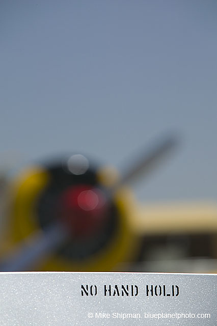 No Hand Hold on North American P-51 Mustang aircraft, with T-3 Texan blurred in background