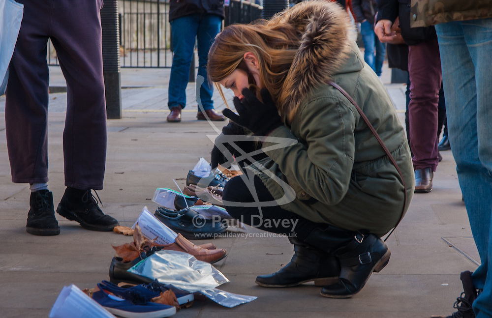 London, December 10th 2014. The shoes of hundreds of victims who died in Ireland, North and South during the Troubles are lined up opposite Downing Street as families demand that a proper investigation into over 3,600 deaths and 40,000 injuries on all sides, sets the truth free. PICTURED: A woman reads the stories of lives long lost.