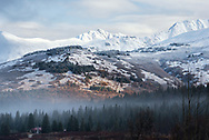 The morning after a fresh autumn snow falls on the mountains along the Seward Highway with a small cabin in the foreground