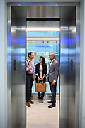 Employees having a conversation inside an elevator as the doors are closing. This image was created as part of a annual report shoot for an international corporation.