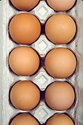 a dozen brown eggs in an egg carton