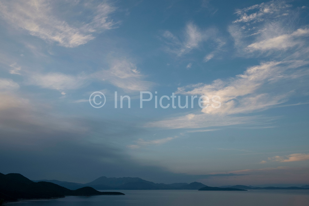 Evening view and cloud formations at sundown out across the Ionian Sea towards the nearby islands and mainland at Rachi, near Kioni in Ithaca Greece. Ithaca, Ithaki or Ithaka is a Greek island located in the Ionian Sea to the west of continental Greece. Ithacas main island has an area of 96 square kilometres. It is the second-smallest of seven main Ionian Islands.