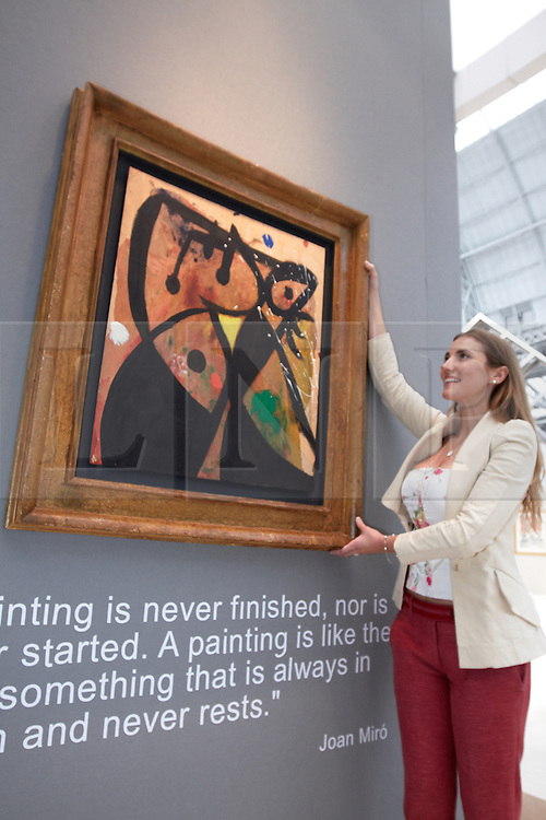 © licensed to London News Pictures. LONDON, UK  08/06/2011. Elvira Pilatti examines a painting by Joan Miro entitled Femme and worth £1 million at the Olympia International Fine Art & Antiques Fair. All 30,000 items on sale from 150 dealers are vetted for authenticity by a panel of experts. The show opens in Olympia tomorrow (Thursday) and runs for 11 days. Please see special instructions for usage rates. Photo credit should read CLIFF HIDE/LNP