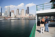 Tourists relax in the sun and photograph the Seattle skyline while crossing Puget Sound on a Washington State Ferry.