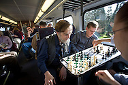 Commuters Christopher Skilton, with beard, Michael Luttmer, on Skilton's right, play chess on Sound Transit's Sounder train as it travels between Seattle and Tacoma, Wash. (AP Photo/John Froschauer)