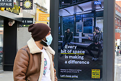 © Licensed to London News Pictures. 23/03/2021. London, UK. A man wearing a protective face covering looks at the government's 'Every bit of space is making a difference' poster in north London on the anniversary of the first Covid-19 lockdown in the UK. The next key date for restrictions easing is Monday 29 March 2021, when the 'Stay at Home' guidance will be dropped. Photo credit: Dinendra Haria/LNP