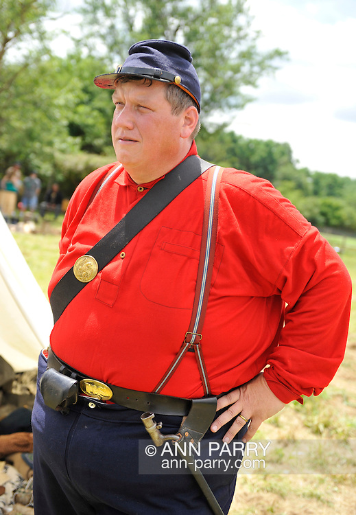 Old Bethpage, New York, USA - July 21, 2012: ROBERT WALKER of Coram, NY, wearing a red wool military shirt in summer, portrays a Private, at re-creation of Camp Scott, a Union Army training camp, at Old Bethpage Village Restoration, to commemorate 150th Anniversary of American Civil War, on Saturday, July 21, 2012.