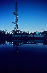 Stock photo of an oil and gas drilling rig reflected in a reserve pit or earthen pit at dusk.