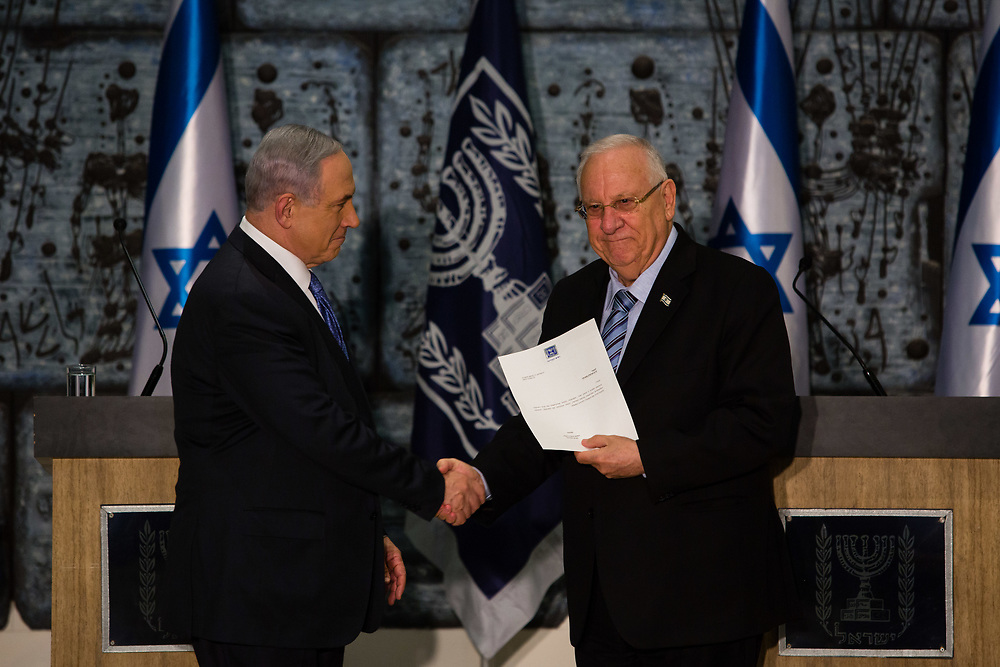 Israeli Prime Minister Benjamin Netanyahu (L) shakes hands with Israeli President Reuven Rivlin as he tasks Netanyahu with forming the next Israeli government, during a ceremony at the President's Residence in Jerusalem, Israel, on March 25, 2015.