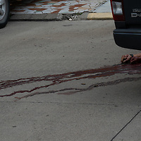 Following a double murder in San Pedro Sula, Honduras one body lays inside the car, another outside the vehicle.