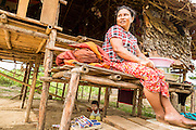 25 MAY 2013 - MAE SOT, TAK, THAILAND: A Burmese woman on the front step of her thatched hut in an unofficial village of Burmese refugees north of Mae Sot, Thailand, on a narrow strip of land about 200 meters deep and 400 meters long that juts into Thailand. The land is technically Burma but it is on the Thai side of the Moei River, which marks most of the border in this part of Thailand. The refugees, a mix of Buddhists and Christians, settled on the land years ago to avoid strife in Myanmar (Burma). For all practical purposes they live in Thailand. They shop in Thai markets and see their produce to Thai buyers. About 200 people live in thatched huts spread throughout the community. They're close enough to Mae Sot that some can work in town and Burmese merchants from Mae Sot come out to their village to do business with them.      PHOTO BY JACK KURTZ