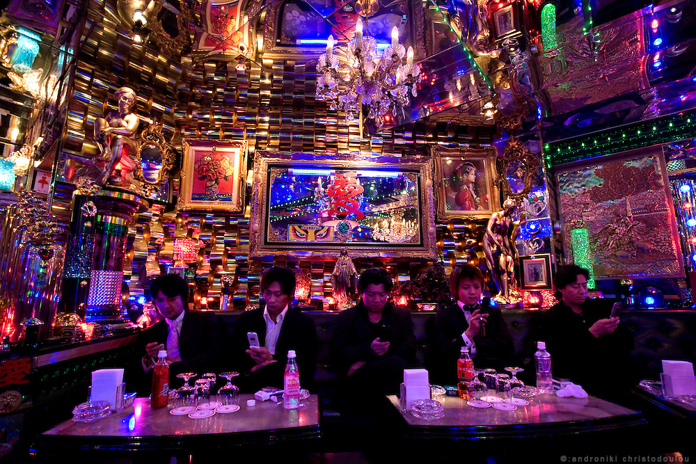 """Hosts communicating with their customers with messages through their mobile phones in club """"Ai"""". Club """"Ai"""" (love in Japanese) is one of the oldest host clubs in Kabukicho entertainment area near Shinjuku. It started functioning 37 years ago, with hosts ready to take care of the needs of their female customers. The customers have to pay from 5000 friendly price for beginners, to millions of yen, depending on how good the host is in pleasing the customer and encouraging her to buy drinks. On top of these a good host can receive expensive gifts from his regular customers.  Tokyo - JAPAN"""