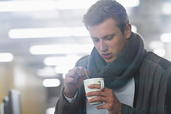 Young businessman drinking coffee and working till late night in office, Freiburg im Breisgau, Baden-Wuerttemberg, Germany