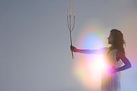 Light woman holding an organic scepter.