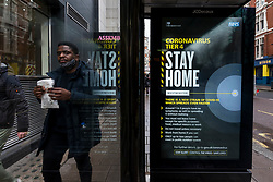 © Licensed to London News Pictures. 21/12/2020. LONDON, UK. A digital sign shows a Tier 4, Stay at Home, alert level message at a bus stop near Leicester Square. Tier 4 restrictions are imposed on much of the UK to combat the ongoing coronavirus pandemic in the light of a recently discovered mutant strain that was discovered to be spreading in the south east of England.  Photo credit: Stephen Chung/LNP