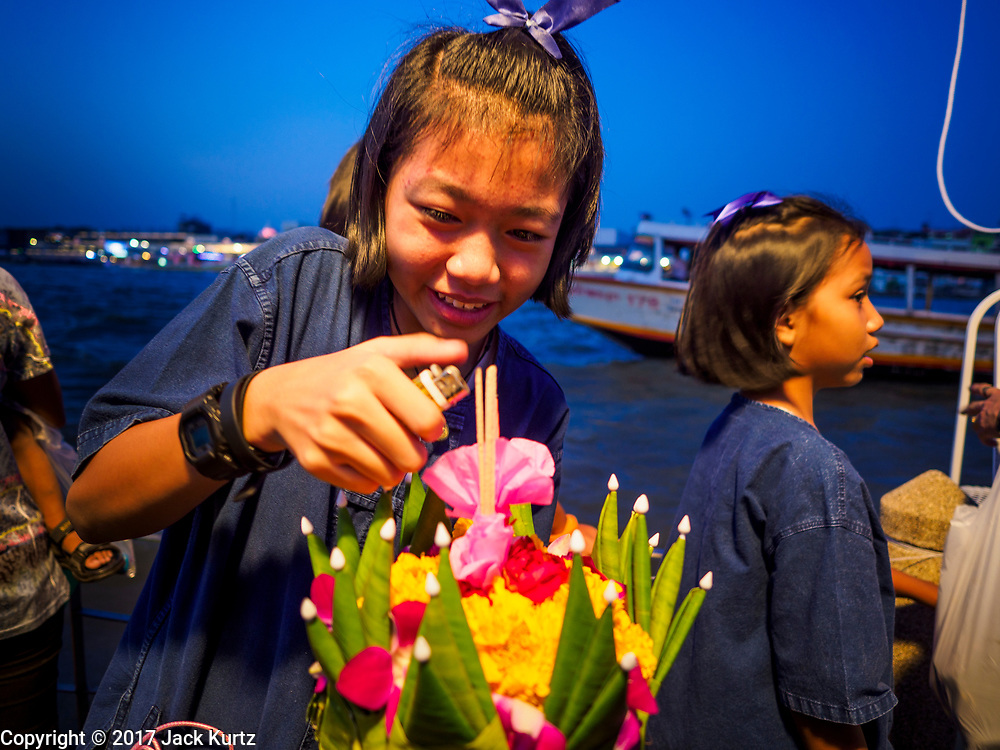 """03 NOVEMBER 2017 - BANGKOK, THAILAND: A girl lights incense in her krathong before floating it during Loi Krathong at Wat Prayurawongsawat on the Thonburi side of the Chao Phraya River. Loi Krathong is translated as """"to float (Loi) a basket (Krathong)"""", and comes from the tradition of making krathong or buoyant, decorated baskets, which are then floated on a river to make merit. On the night of the full moon of the 12th lunar month (usually November), Thais launch their krathong on a river, canal or a pond, making a wish as they do so. Loi Krathong is also celebrated in other Theravada Buddhist countries like Myanmar, where it is called the Tazaungdaing Festival, and Cambodia, where it is called Bon Om Tuk.     PHOTO BY JACK KURTZ"""