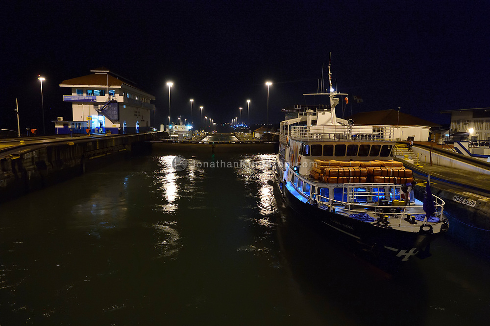 A small passenger ship in the Gatun locks at night, on the Atlantic side of the Panama Canal, Panama.