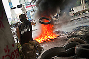 18 MAY 2010 - BANGKOK, THAILAND: An anti government protester throws a tire on a burning tire barricade at Din Daeng Intersection in Bangkok Tuesday. The intersection has been under periodic sniper fire from unidentified snipers near Thai military lines. Violent unrest continued in Bangkok again Tuesday nearly a week after Thai troops started firing on protesters and Bangkok residents took to the streets in violent protest against the government. Tuesday was not as violent as previous days however. Although protesters continued to set up roadblocks and flaming tire barricades across parts of the city, there was not as much gunfire from the government lines. The most active protesters were at the Din Daeng Intersection about a mile from the Red Shirts' Ratchaprasong camp.  PHOTO BY JACK KURTZ