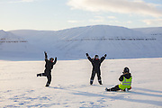 Glaciologist Nick Hulton takes pictures for UNIS students playing on Rabotbreen, Svalbard, on a class field trip by snowmobile to Tunabreen.