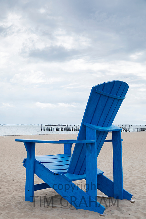 Oversize large Adirondack chair in bright blue colour on the beach overlooking Atlantic Ocean at Provincetown, Cape Cod, USA