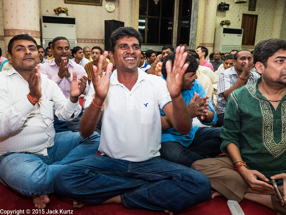 05 SEPTEMBER 2015 - BANGKOK, THAILAND:  Men sing and pray during Janmashtami services in the Vishnu Temple in Bangkok. Janmashtami is the annual celebration of the birth of the Hindu deity Krishna, the eighth avatar of Vishnu. Hindus celebrate Janmashtami by fasting, worshipping Krishna and staying up until midnight, the time when Krishna is believed to have been born. At midnight they pray and exchange small gifts.    PHOTO BY JACK KURTZ