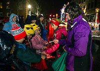 Santa's Helpers hand out candy to children lining the streets downtown during the annual Holiday Parade on Saturday evening. (Karen Bobotas/for the Laconia Daily Sun)