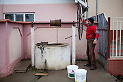 A man is getting drinking water from a fountain located at the main road in Marginenii de Jos.