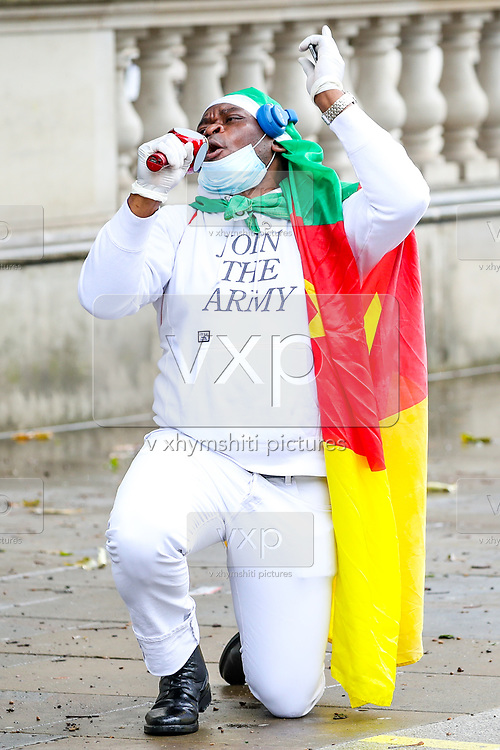 """A Cameroonian activist gestures as he protests in Whitehall, nearby Downing Street prior to French President Emanuel Macron's visit in London, on Thursday, June 18, 2020. They say France is involved in the looting of Cameroon and Africa. A letter addressing the press and members of the public says: """"We are here to tell Mr Macron this is unacceptable. Enough is enough!"""".<br /> For his first foreign trip since lockdown, Emmanuel Macron will be in London to mark the 80th anniversary of de Gaulle's « appel de Londres », as well as cement Franco-UK ties at a strained time due to Brexit. (Photo/ Vudi Xhymshiti)"""