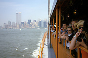 Tourists on a New York ferry with Manhattan in the background