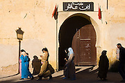 Pedestrians walk along the palace walls in Meknes, Morocco.