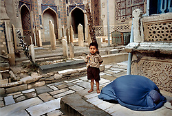 A woman prays with her son at the Kowaja Abdullah Ansaar shrine, the main Sufi shrine in Herat, which was named after a poet.