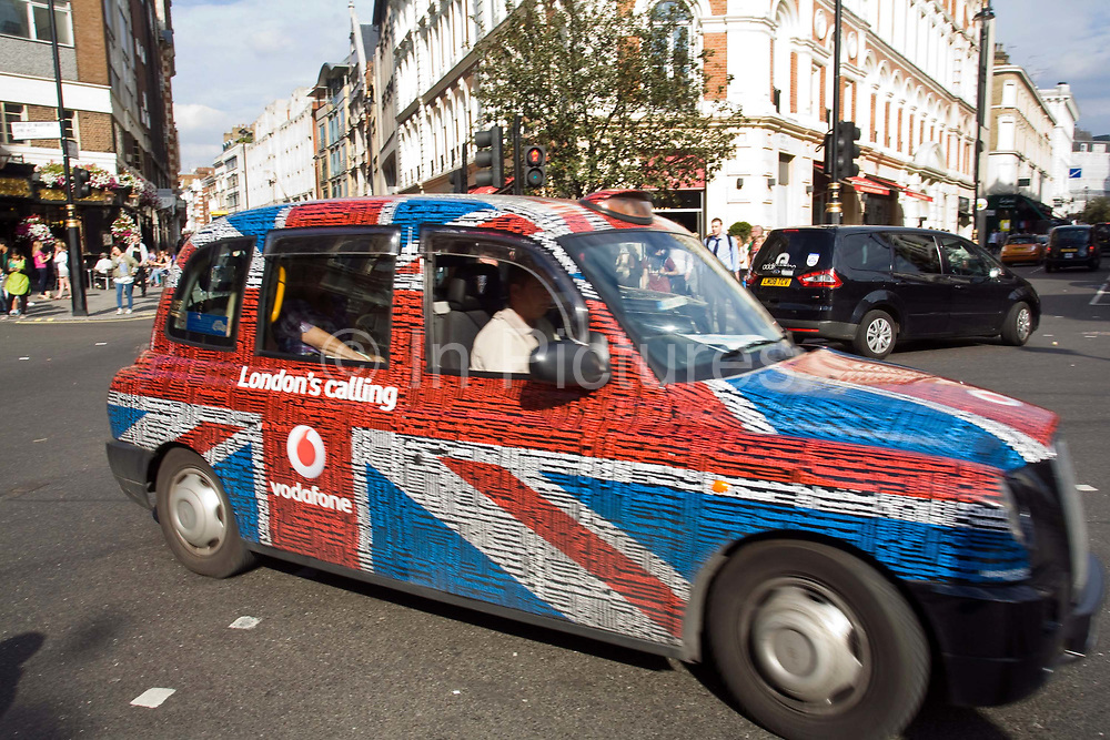 A London taxi decorated in a Union Jack advertisement for Vodafone turns a corner near Covent Garden in London, UK