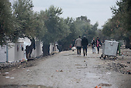 Syrians walk on the muddy path at Kara Tepe camp on Lesbos, Greece. The camp was set up to temporarily house some of the hundreds of thousands of refugees and other migrants that had arrived on Lesbos via neighboring Turkey, on their way to mainland Europe to seek asylum.