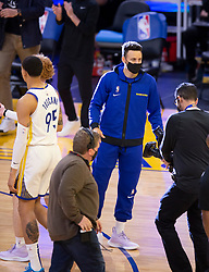 Mar 26, 2021; San Francisco, California, USA; Injured Golden State Warriors guard Stephen Curry, center, greets his teammates during a timeout in the third quarter of an NBA basketball game against the Atlanta Hawks at Chase Center. Curry has missed the last four games with a bruised tailbone. Mandatory Credit: D. Ross Cameron-USA TODAY Sports