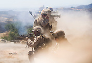 Dust and fumes swirl around Marines after launching several AT-4 rockets simultaneously during live-fire exercises for the 2nd Battalion, 5th Marine Regiment at Camp Pendleton.