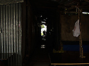 04 SEPTEMBER 2013 - BANGKOK, THAILAND:  People walk through the corrugated metal housing for workers on the construction site of a new high rise apartment / condominium building on Soi 22 Sukhumvit Rd in Bangkok. Most of the workers at the site are Cambodian immigrants.    PHOTO BY JACK KURTZ