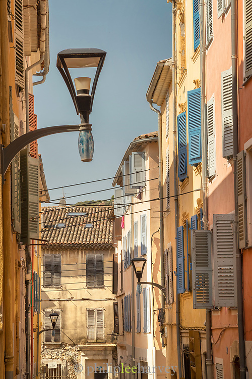 Narrow street with old tenement houses with shuttered windows, Old Town, Vallauris, France.