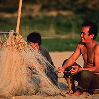Fisherman tends to net on beach, Ban Pak Ou, Luang Phrabang, Laos