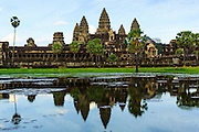 """02 JULY 2013 - ANGKOR WAT, SIEM REAP, SIEM REAP, CAMBODIA:  The west side of Angkor Wat late in the afternoon. Angkor Wat is the largest temple complex in the world. The temple was built by the Khmer King Suryavarman II in the early 12th century in Yasodharapura (present-day Angkor), the capital of the Khmer Empire, as his state temple and eventual mausoleum. Angkor Wat was dedicated to Vishnu. It is the best-preserved temple at the site, and has remained a religious centre since its foundation– first Hindu, then Buddhist. The temple is at the top of the high classical style of Khmer architecture. It is a symbol of Cambodia, appearing on the national flag, and it is the country's prime attraction for visitors. The temple is admired for the architecture, the extensive bas-reliefs, and for the numerous devatas adorning its walls. The modern name, Angkor Wat, means """"Temple City"""" or """"City of Temples"""" in Khmer; Angkor, meaning """"city"""" or """"capital city"""", is a vernacular form of the word nokor, which comes from the Sanskrit word nagara. Wat is the Khmer word for """"temple grounds"""", derived from the Pali word """"vatta."""" Prior to this time the temple was known as Preah Pisnulok, after the posthumous title of its founder. It is also the name of complex of temples, which includes Bayon and Preah Khan, in the vicinity. It is by far the most visited tourist attraction in Cambodia. More than half of all tourists to Cambodia visit Angkor.         PHOTO BY JACK KURTZ"""