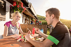 Young couple eating salad at alpine cabin, Kampenwand, Bavaria, Germany