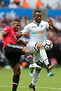 Antonio Valencia of Manchester Utd challenges Jordan Ayew of Swansea city ®. Premier league match, Swansea city v Manchester Utd at the Liberty Stadium in Swansea, South Wales on Saturday 19th August 2017.<br /> pic by  Andrew Orchard, Andrew Orchard sports photography.
