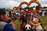 Three women pose for a photo during a party in the main square of Boca Colorado, Peru. Boca Colorado is a town formed entirely by mining activity in the Peruvian Amazon.