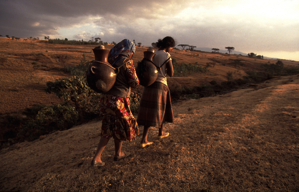 Women carrying water from well back to their village in the Ethiopian highlands<br /> <br /> Pic Steve Morgan