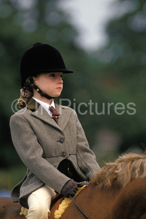 A young girl sits on her pony, waiting for the beginning of her race at a local gymkhana, on 17th September 1999, in Cheltenham, England. Wearing a smart herringbone patterned jacket, regulation jodhpurs and holding a crop to encourage the horse to perform a series of trick and races, she sits calmly awaiting the next event. The word gymkhana is an Indian Raj term that referred to a place where sporting events took place to test the skill of the competitors. In the UK and east coast of the US, the term gymkhana now almost always refers to an equestrian event for riders on horses, often with the emphasis on childrens participation such as those organised here by the Pony Club. Gymkhana classes include timed speed events such as barrel racing, keyhole, keg race also known as down and back, flag race, and pole bending.