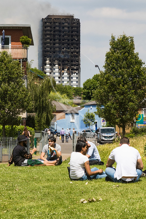 London, June 14th 2017. A fire rages through a residential tower block, Grenfell Tower, in Kensington, West London, with the entire building engulfed in flames. More than 200 firefighters are attending the incident and there are reports of people trapped inside. No figures are available as to casualties. PICTURED: Office workers relax in the sunshine as beyond them the tower block continues to burn.