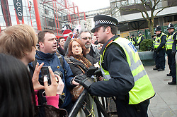 """Police deal with one of the demos speakers as he sits on the """"ring of Steel"""" and chants anti Government slogans  in  Barkers Pool, outside Sheffield city Hall where the Liberal Democrats are holding their Party conference Conference Sheffield Saturday.12 March 2011.Images © Paul David Drabble"""