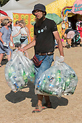 A man collects empties to earn money from the deposit scheme keeping the site clean in the process - The 2018 Latitude Festival, Henham Park. Suffolk 15 July 2018