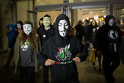 © Licensed to London News Pictures . 05/11/2015 . Manchester , UK . Protesters wearing Guy Fawkes masks at an Anonymous demonstration leave the Arndale Centre in Manchester , UK , this evening (5th November 2015) . Photo credit : Joel Goodman/LNP