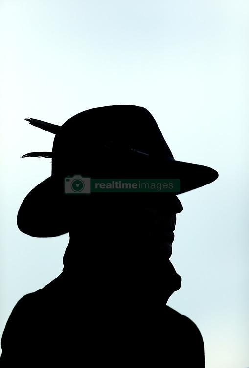 A silhouette of a racegoer wearing a hat during St Patrick's Thursday of the 2018 Cheltenham Festival at Cheltenham Racecourse.