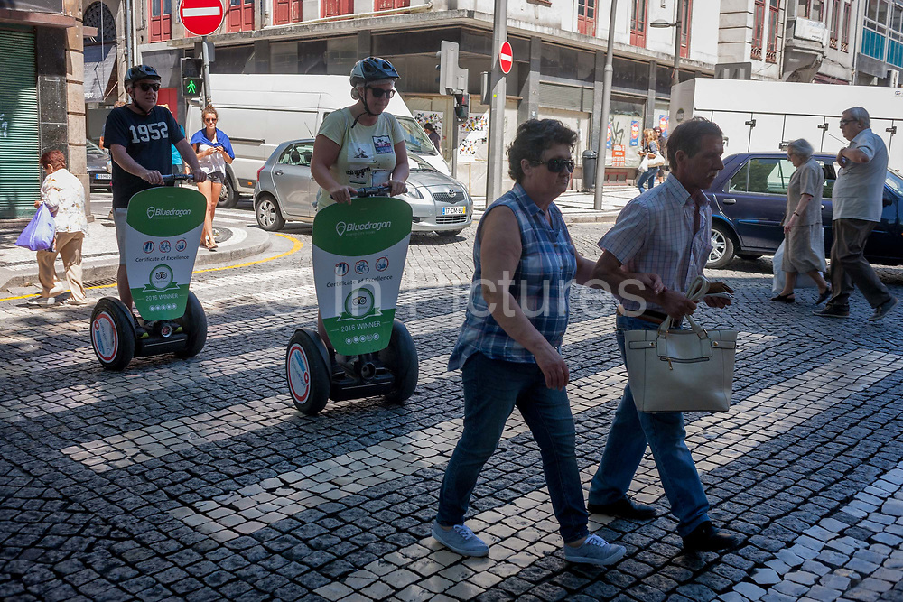 Two pedestrians cross the cobbled Rua Sa da Bandeira, followed closely by a pair of Segway riding tourists, on 21st July, in Porto, Portugal. Segway tours have become controversial additions to the European city sightseeing scene, already being banned in Barcelona and Prague. But in Portuguese cities like Lisbon and Porto, Segway travellers still share narrow and busy streets and often, pavements, with locals on foot.